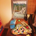 Frogtown still life: Patrick's Lavender Country painting, Justin's dice collection, and Jack Vance novels.